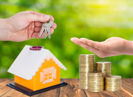 Sale and rental properties,loans for real estate concept. A realtor hand gives keys for home with stack of coins