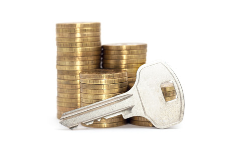 A keys with stack of coins isolated on white background.