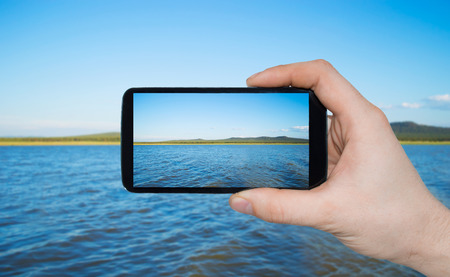 A man hand holding smart phone making photo on smartphone mobile closeup landscape view Stock Photo