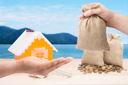 Sale and rental properties loans for real estate concept. Hand with bag  giving money to another