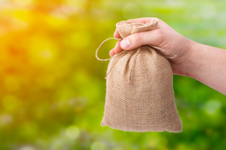 A businessman hand giving a bag from sacking on bokeh background