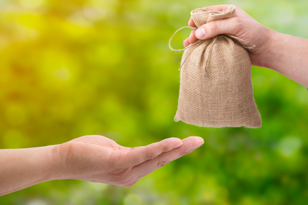 Loans for real estate concept. Hand with bag giving money to another hand on green and yellow bokeh background