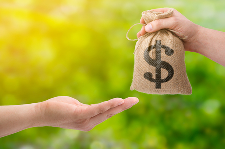 Loans for real estate concept. Hand with bag dollar sign giving money to another hand on green and yellow bokeh background Stock Photo