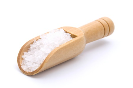 Sea salt in wooden scoop isolated on white background