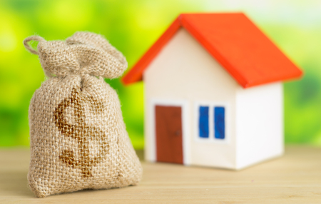 A home with red roof on green background with bag from sack with dollar sign and money inside bag concept of selling or buy home Stock Photo