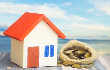 A home with red roof on blue background with bag from sack with dollar sign and money inside bag concept of sell or buy home