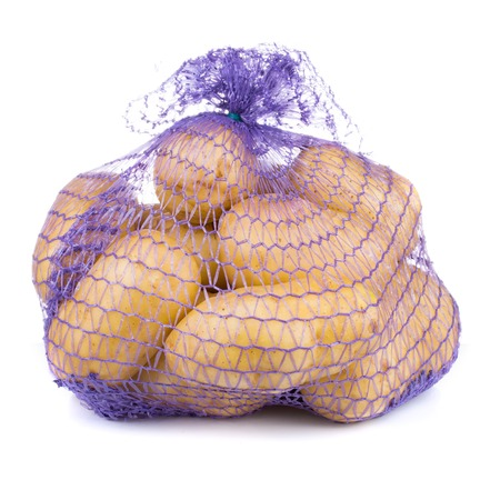 raw potatoes in a blue net bag isolated on white background Imagens