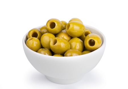 Green olives in a white ceramic bowl isolated on white background. Stock fotó