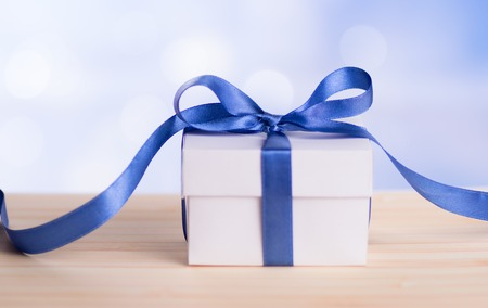 Christmas gift box with blue ribbon bow and bokeh background.