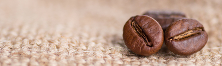 Cloceup of brown roasted coffee beans seeds on burlap textile background black caffeine drink and energy mocha ingredient Foto de archivo