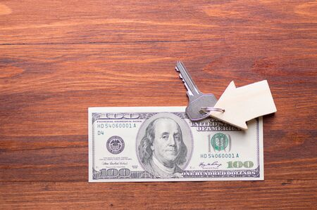 Small Model wooden House and Keys on One Hundred Dollar Bills on wooden background