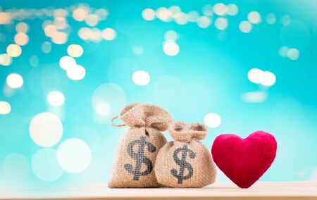 two bags with dollars and a red heart on a wooden table and a blue background with bokeh