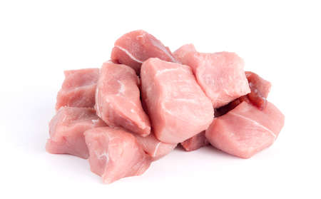 Pile of pork uncookes chopped cubes close up isolated on white background Stock Photo