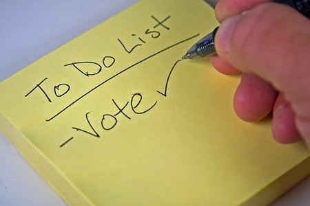 Yellow sticky note with someone writing vote with a pen photo