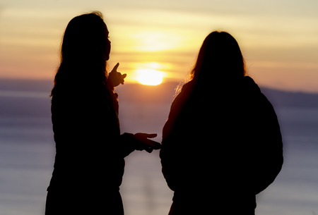 Silhouette of girls watching sunset Standard-Bild