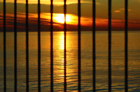 waiting convict: The sunset in the evening at the Baltic sea behind the bars