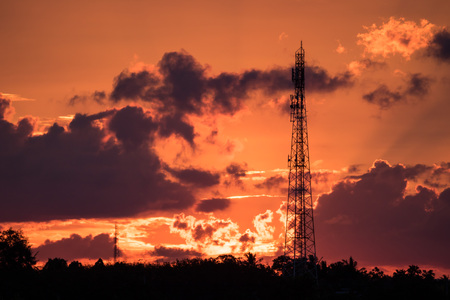 Several radio towers with sunset sky in background Stock Photo