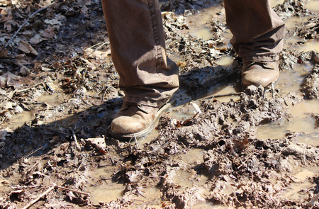 slog: A man with boots walking on a muddy trail in February