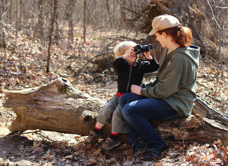 Blond boy looking through binoculars at his mother while sitting on a log  photo