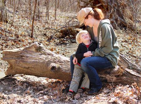 Blond boy and his mother smiling and enjoying a sunny day in late February sitting on a log Imagens