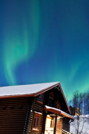 Northern Lights  Aurora Borealis  above a cabin photo