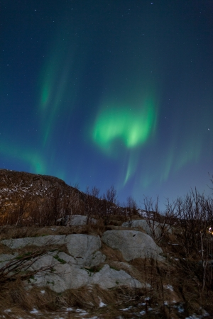 Aurora Borealis  Northern lights  behind mountains photo