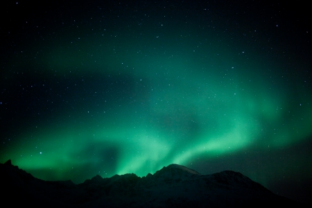 Aurora Borealis  Northern lights  behind mountains