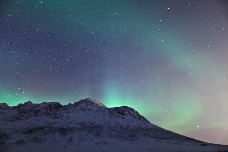 arctic zone: Aurora Borealis  Northern lights  behind mountains