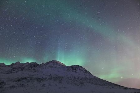 Aurora Borealis  Northern lights  behind mountains photo