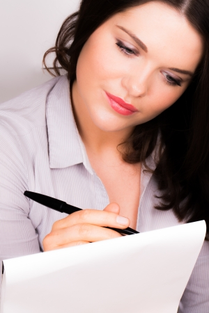 jot: Young beautiful professional female writing on pad