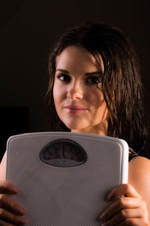 Young fit female trainer with scales  photo