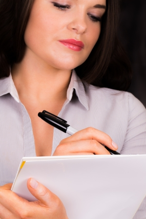 jot: Young professional female writing on pad