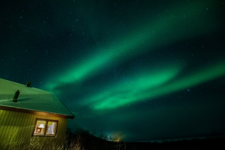 Northern lights above a cabin in Sweden