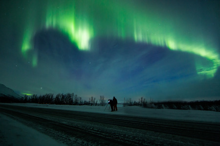 arctic zone: Northern lights above road in Norway