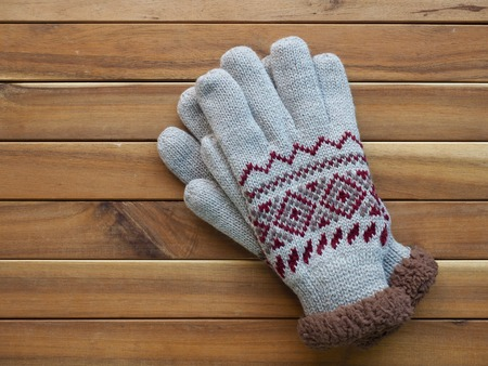 Wooden background and winter gloves