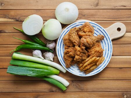 Fried chicken, French fries, Fresh organic vegetables, onion, wave, pepper, garlic Imagens