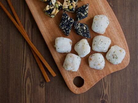 Korean traditional sweets and cookies, Songpyeon, Honey-filled Rice Cake, Sesame glutinous rice cake on wooden desk. Reklamní fotografie