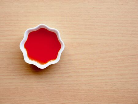 Red chili oil in white porcelain bowl, red pepper oil