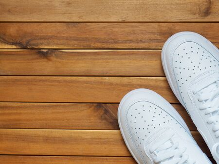 White male sneakers with wooden board background