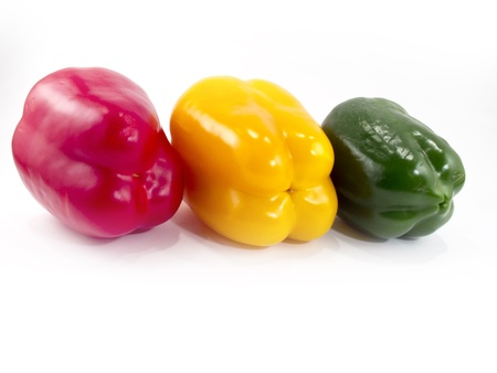 Three peppers of different colors with a white background photo