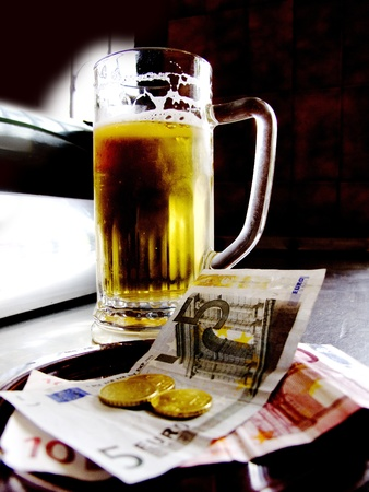 a mug of beer in a bar with money exchange photo
