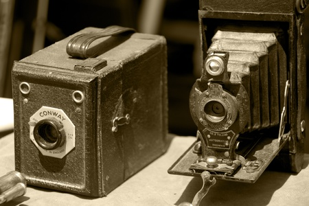 two very old photo cameras in sepia