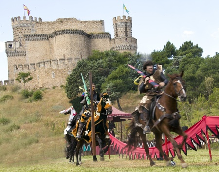 vestidos de epoca: caballero medieval sobre su caballo al galope Editorial