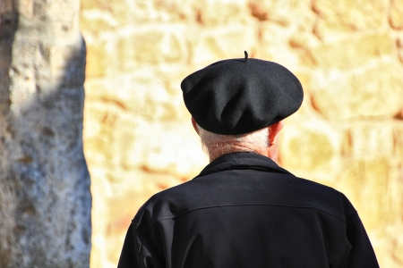 old man walking with beret photo