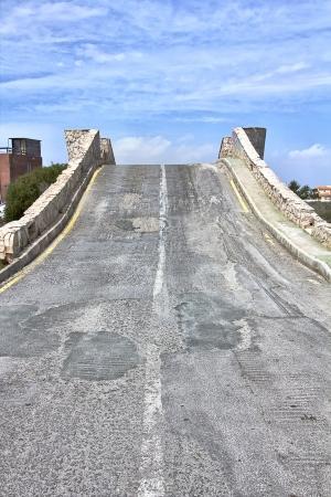 old road climbs a steep bridge photo