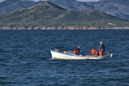 fishermen fishing in the sea in a small boat photo