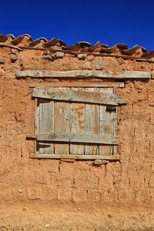 mud house: old wooden window in the house of adobe and mud Stock Photo