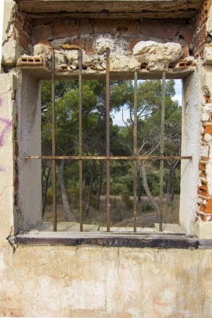 Old window with iron bars at home in ruins photo