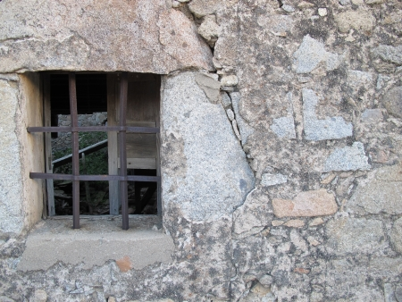 Old window with iron bars in stone wallc photo
