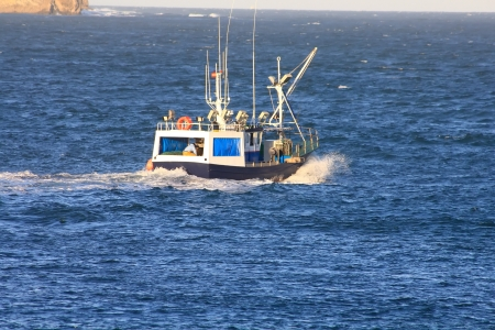 small fishing boat sailing near the coast in a blue sea photo